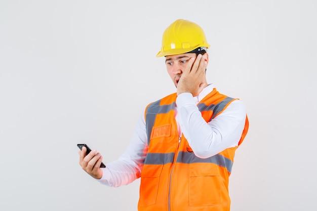 シャツを着たビルダーの男、頬に手を当ててスマートフォンを見て、驚いたように見える制服、正面図。
