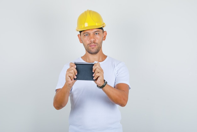 Строитель человек в белой футболке, шлем, держащий мини-ноутбук, вид спереди.