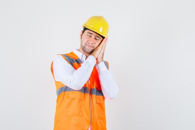 Uomo del costruttore che si appoggia sui palmi come cuscino in camicia, uniforme e che sembra assonnato. vista frontale.