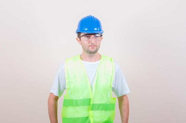 Tシャツ、ヘルメットで目をそらし、賢明に見えるビルダーの男