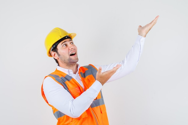 Builder man looking up while showing something away in shirt, uniform and looking cheery. front view.