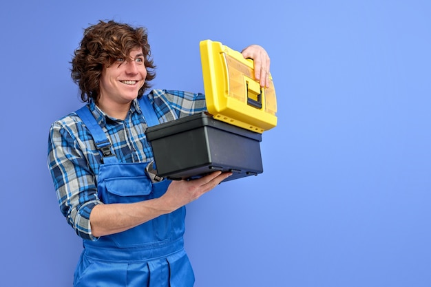 Builder man opening tools box with surprised expression on face, curly caucasian guy in blue coveralls isolated over purple studio background.