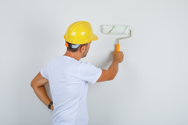 Строитель человек рисует стену с роликом в белой футболке, шлеме и выглядит занятым, вид сзади.
