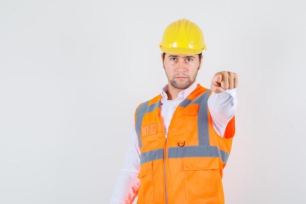 ビルダーの男がシャツを着てあなたに指を向け、制服を着て真面目な顔つき、正面図。