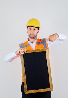 Uomo del costruttore che indica il dito alla lavagna in vestiti classici, giacca, casco e che sembra serio. vista frontale. Foto Gratuite