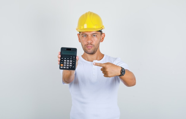 Builder man pointing finger at calculator in white t-shirt, helmet, front view.