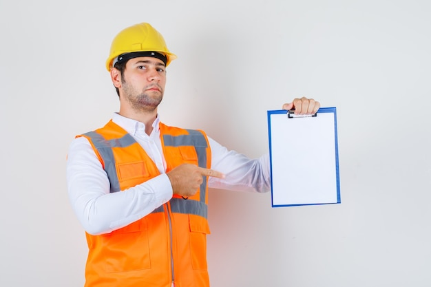 Builder man pointing finger at clipboard in shirt, uniform and looking serious. front view.