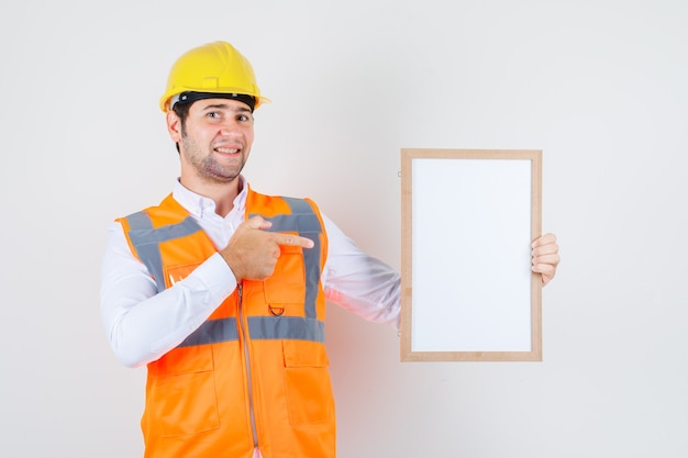 Builder man pointing finger at white board in shirt, uniform and looking merry , front view.