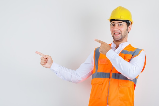 Builder man pointing fingers to side in shirt, uniform and looking cheerful , front view.