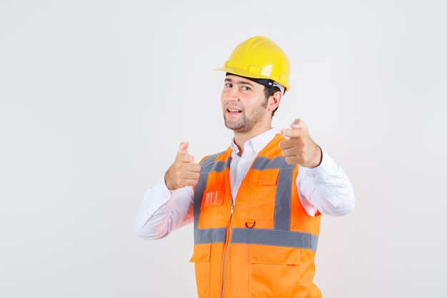 Builder man pointing to invite in shirt, uniform and looking positive. front view.