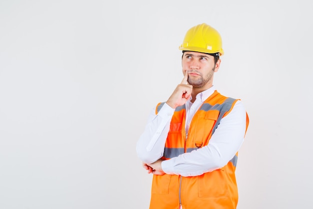 Builder man putting finger near mouth in shirt, uniform and looking pensive. front view.