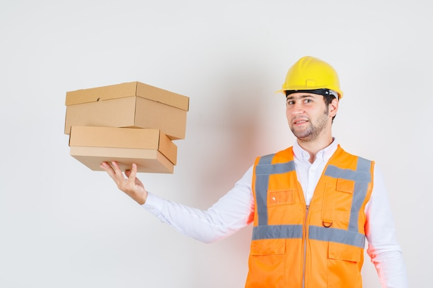 Builder man in shirt, uniform holding cardboard boxes and looking glad , front view.