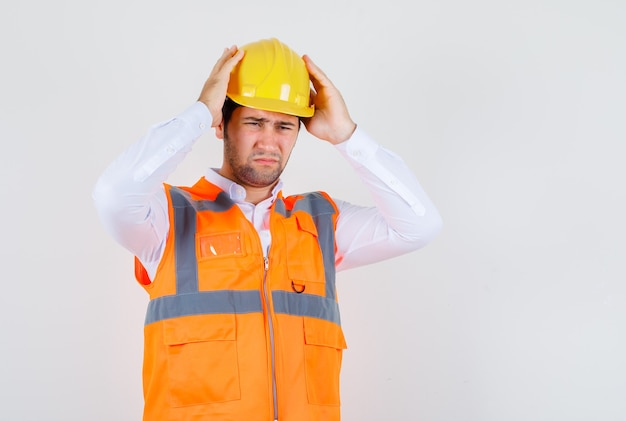 Builder man in shirt, uniform holding his helmet and looking painful , front view.