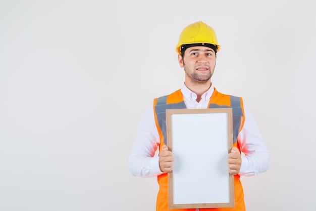 Uomo del costruttore in camicia, uniforme che tiene il bordo bianco e che sembra positivo, vista frontale.