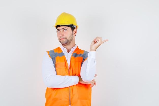 Uomo del costruttore in camicia, uniforme che osserva in su mentre punta lontano e guardando pensieroso, vista frontale