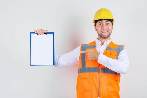 Uomo del costruttore in camicia, dito puntato uniforme negli appunti e che sembra gioioso, vista frontale.