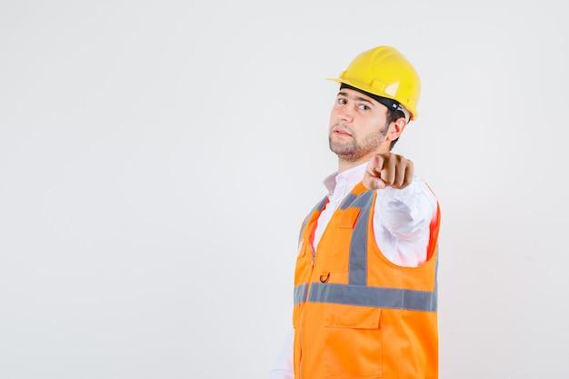 Uomo del costruttore in camicia, dito puntato uniforme e guardando fiducioso, vista frontale.