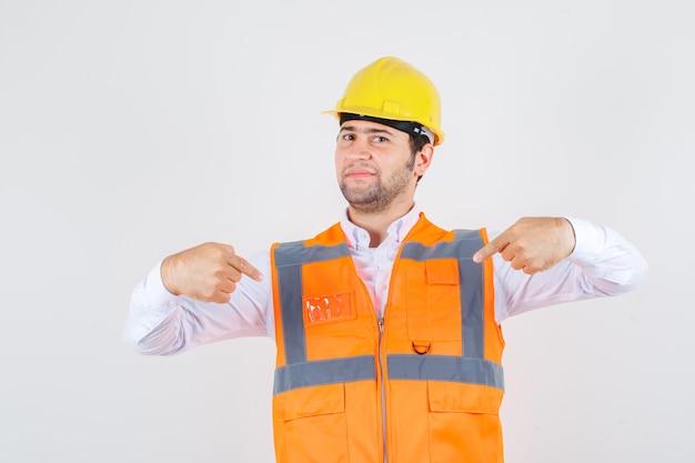 Uomo del costruttore in camicia, uniforme che punta a se stesso e che sembra fiducioso, vista frontale.
