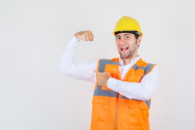 Builder man in shirt, uniform pointing at his muscle and looking strong , front view.
