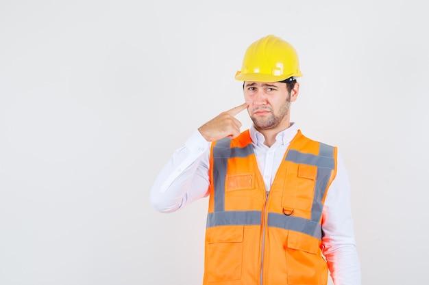 Uomo del costruttore in camicia, uniforme che mette il dito sulla guancia e che sembra triste, vista frontale.