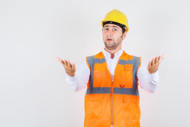 Uomo del costruttore in camicia, uniforme che alza le braccia nel gesto interrogativo e che sembra perplesso, vista frontale.