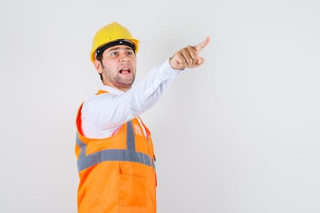 Uomo del costruttore in camicia, uniforme che mostra qualcosa di lontano e che sembra preoccupato, vista frontale.