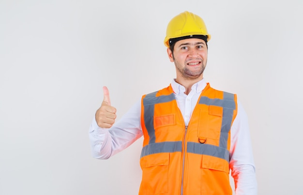 Builder man in shirt, uniform showing thumb up and looking cheerful , front view.