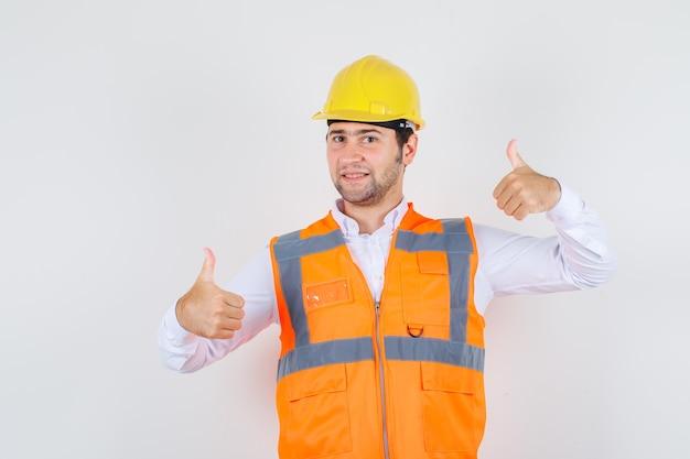 Uomo del costruttore in camicia, uniforme che mostra i pollici in su e che sembra felice, vista frontale.