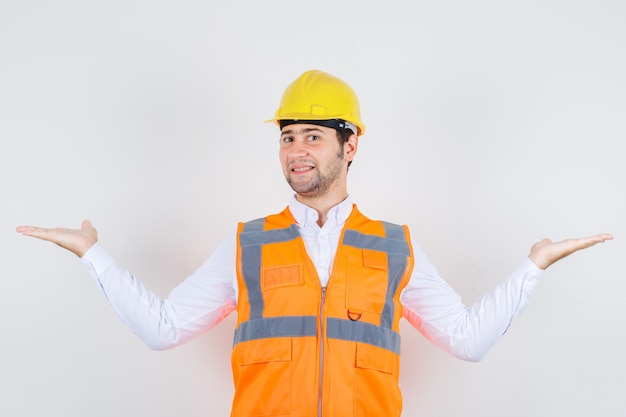 Builder man in shirt, uniform spreading arms wide like catching something and looking happy , front view.