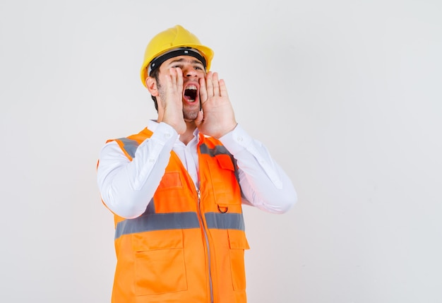 Builder man shouting or announcing something in shirt, uniform front view.
