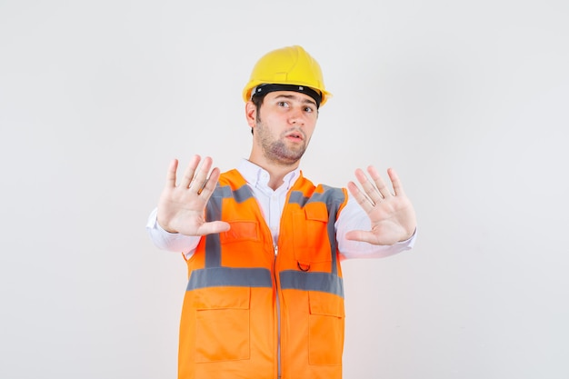 Builder man showing enough gesture in shirt, uniform and looking serious. front view.