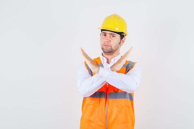 シャツに身振りを示さず、制服を着て暗い顔をしているビルダーの男。正面図。