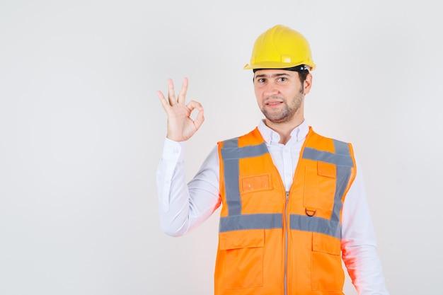 Строитель человек показывает нормально жест в рубашке, униформе и рад, вид спереди.