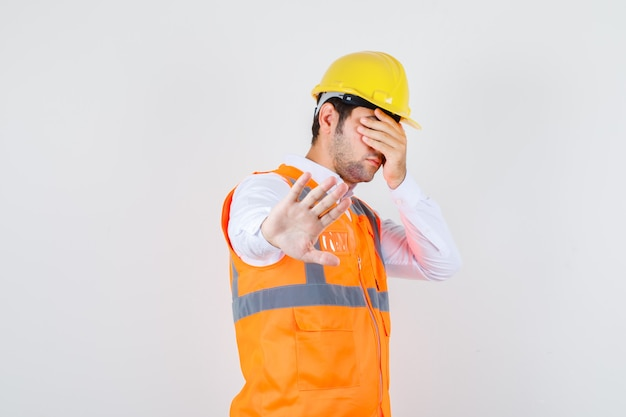 Builder man showing stop gesture while covering eyes in shirt, uniform front view.