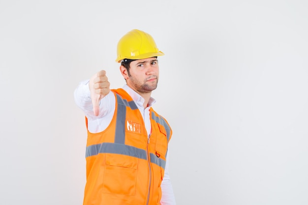 Uomo del costruttore che mostra il pollice giù in camicia, uniforme e che sembra scontento. vista frontale.