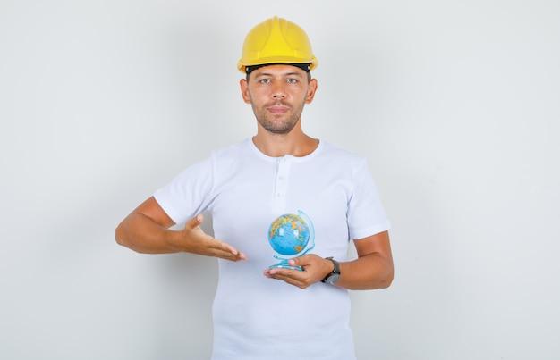 Строитель человек показывает глобус мира в белой футболке, шлеме, вид спереди