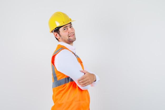 シャツを着て腕を組んで立っているビルダーの男、制服を着て陽気に見えます。