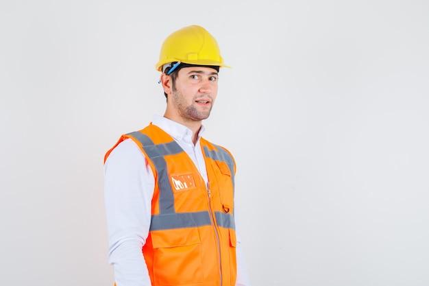 シャツの彼の耳の後ろに鉛筆で立っているビルダーの男、制服と前向きに見える、正面図。