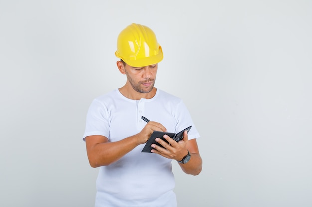 Builder man taking notes on mini notebook in white t-shirt, helmet and looking busy, front view