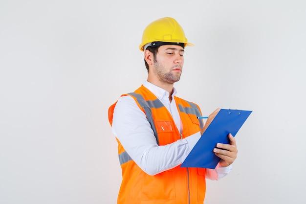 Строитель человек делает заметки в буфер обмена в рубашке, униформе и выглядит занятым, вид спереди.
