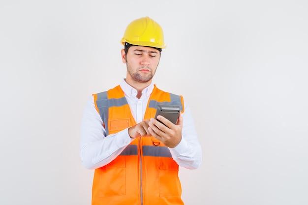 Uomo del costruttore utilizzando la calcolatrice in camicia, uniforme e sembra occupato, vista frontale.