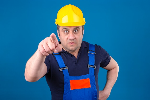 Мужчина-строитель в строительной форме и защитном шлеме недовольно и разочарованно смотрит в камеру, злой и разъяренный на вас над изолированной синей стеной