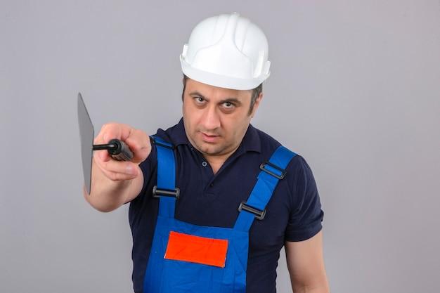 Человек-строитель в строительной форме и защитном шлеме, указывая на камеру с шпателем, серьезно смотрит на изолированную белую стену