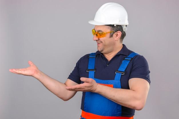 Человек-строитель в строительной форме и защитном шлеме, указывая в сторону руками и открытыми ладонями, представляет рекламу, счастливую и уверенную, улыбаясь над изолированной белой стеной