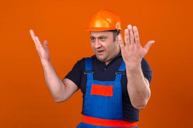 작성기 남자 건설 유니폼과 안전 헬멧을 착용 격리 된 오렌지 벽에 분노와 팔을 제기