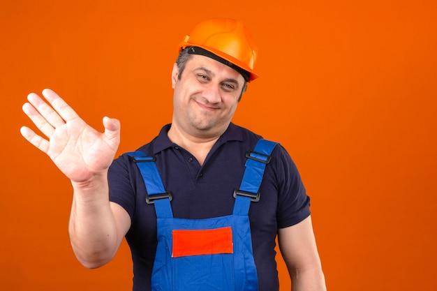 Человек-строитель в строительной форме и защитном шлеме улыбается и счастливо машет рукой над изолированной оранжевой стеной