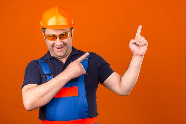 2つの手と指で孤立したオレンジ色の壁を指して幸せそうな顔を浮かべて建設制服と安全ヘルメットを身に着けているビルダー男