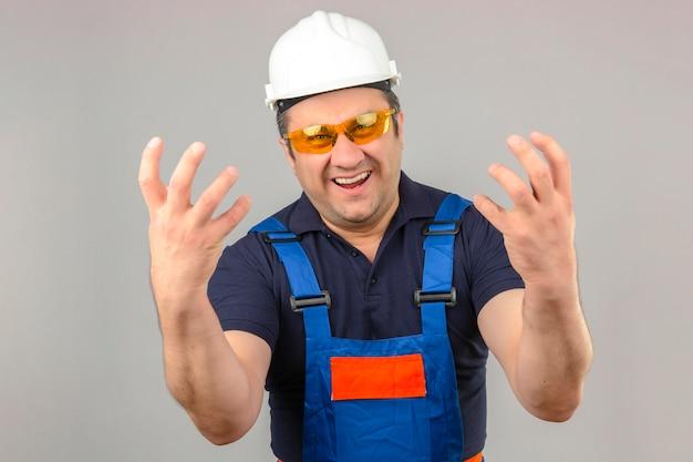 Человек-строитель в строительной форме и защитном шлеме стоит сумасшедшим и безумным с агрессивным выражением лица и поднятыми руками над изолированной белой стеной