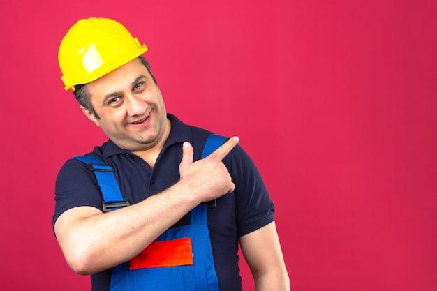 Человек-строитель в строительной форме и защитном шлеме стоит с большой улыбкой на лице, указывая в сторону с пальцем над изолированной розовой стеной