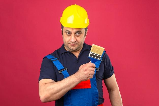 孤立したピンクの壁の上の顔に笑顔でペイントブラシで立っている建設の制服と安全ヘルメットを身に着けているビルダー男